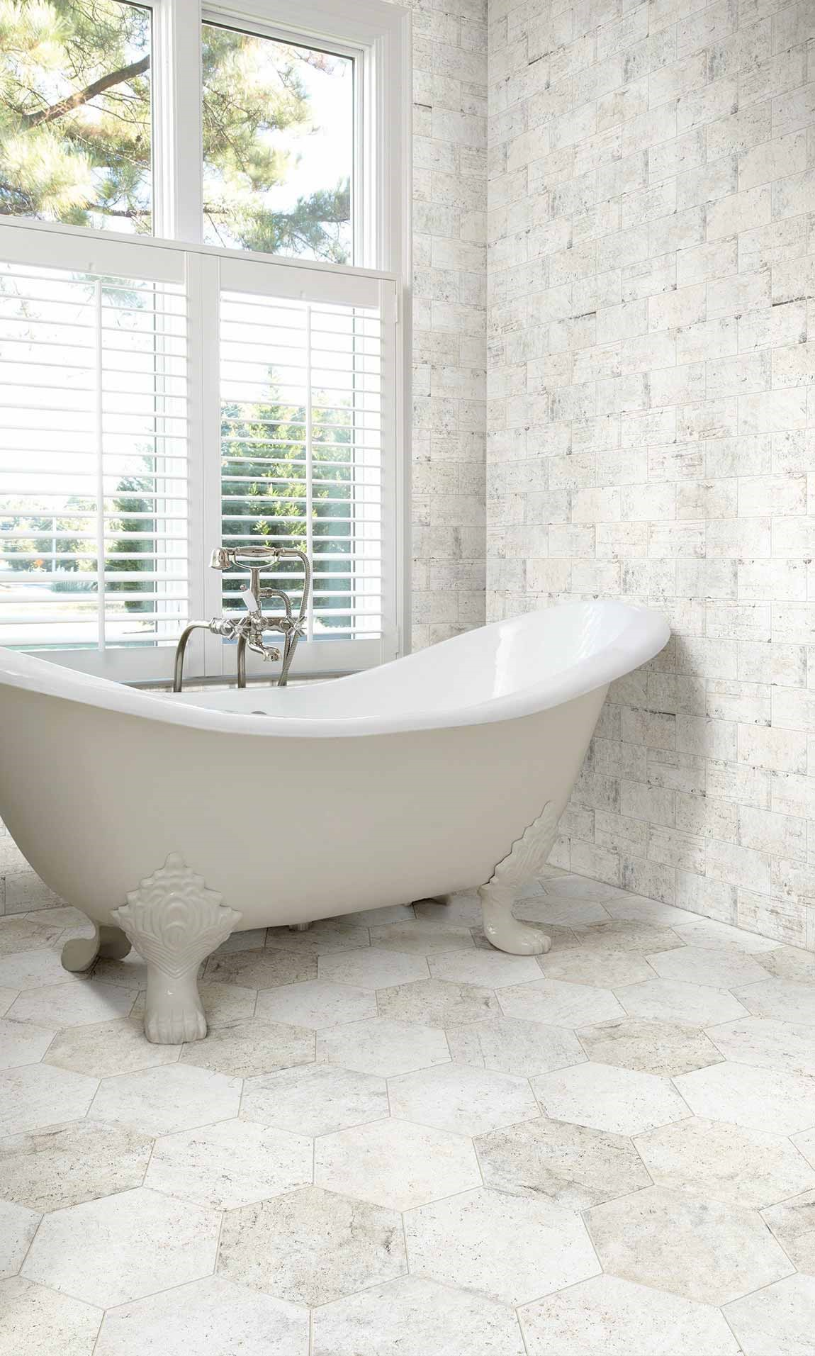 reestanding bathtub in light colored bathroom with ceramic tile